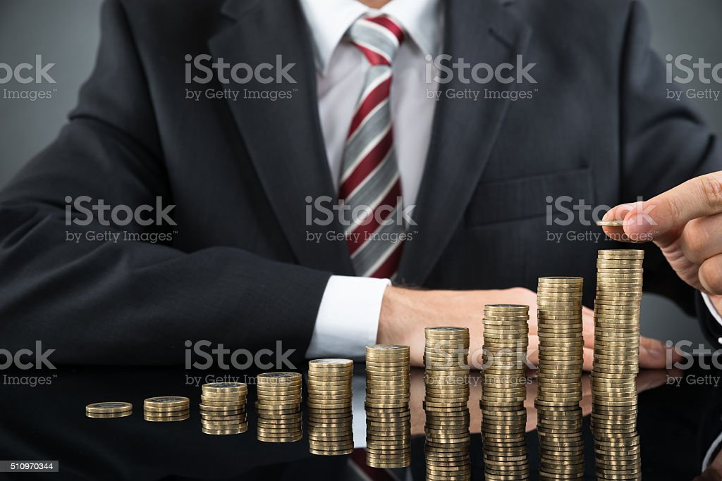 Businessman Placing Coin Over Stack Of Coins stock photo
