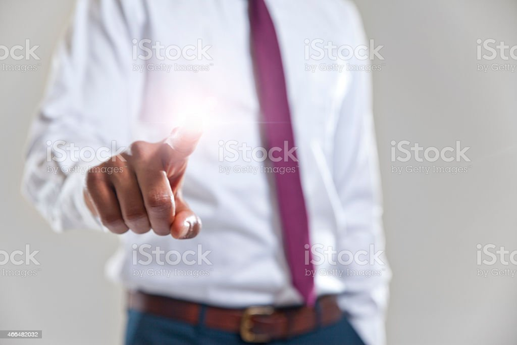 Businessman placing his pointer finger on a touch screen stock photo
