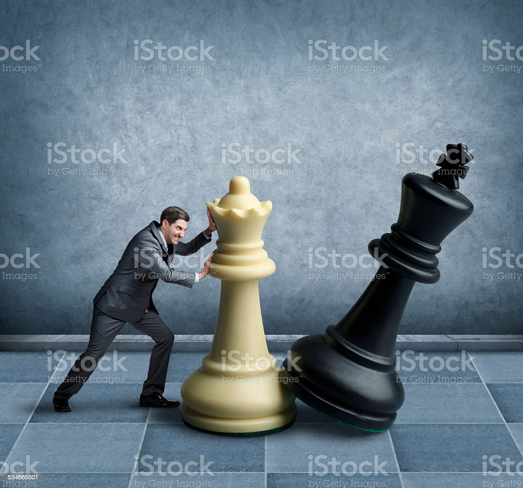 Businessman playing chess with oversized chess pieces stock photo