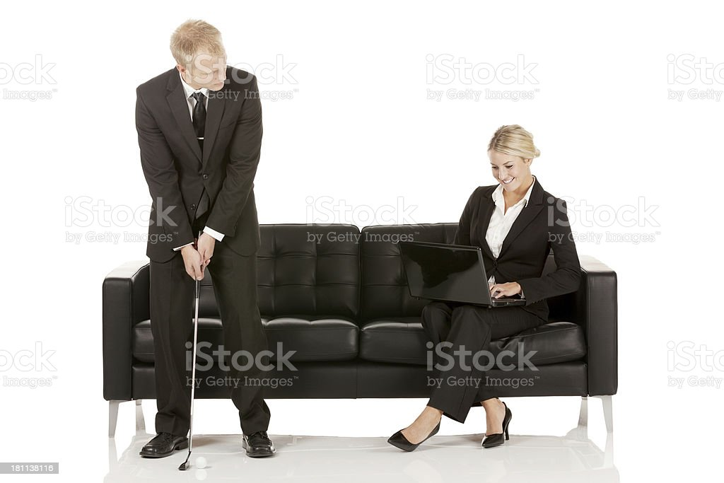 Businessman playing golf and colleague using laptop royalty-free stock photo