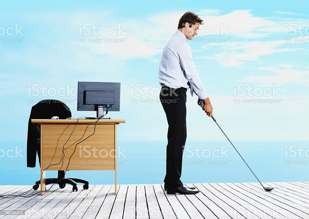 Businessman playing golf on jetty royalty-free stock photo