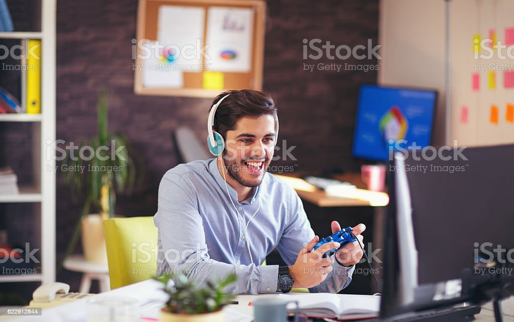 Businessman playing videogames in his office stock photo