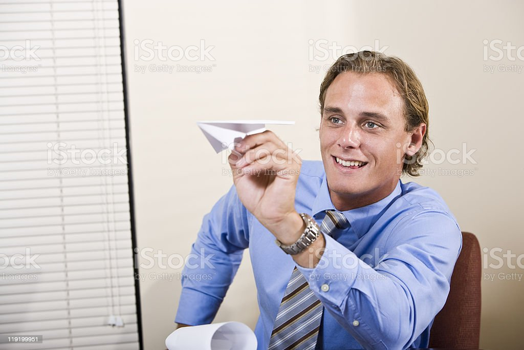 Businessman playing with paper airplane royalty-free stock photo