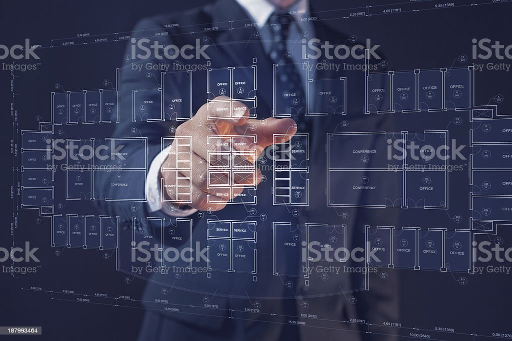 Businessman pointing a display with an office architecture interactive blueprint stock photo