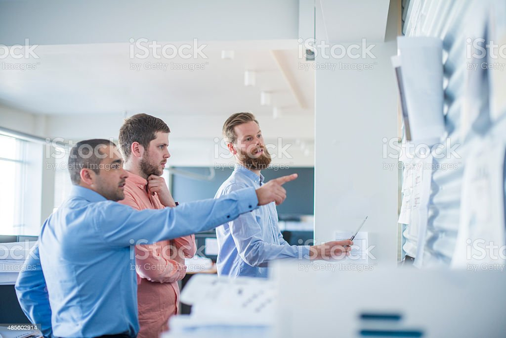 Businessman pointing at blueprint while standing with colleagues stock photo