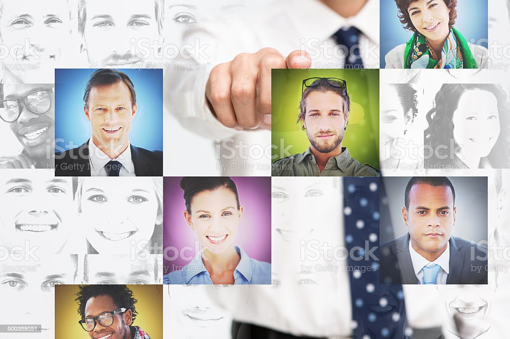 Businessman pointing at digital interface presenting profile pictures stock photo