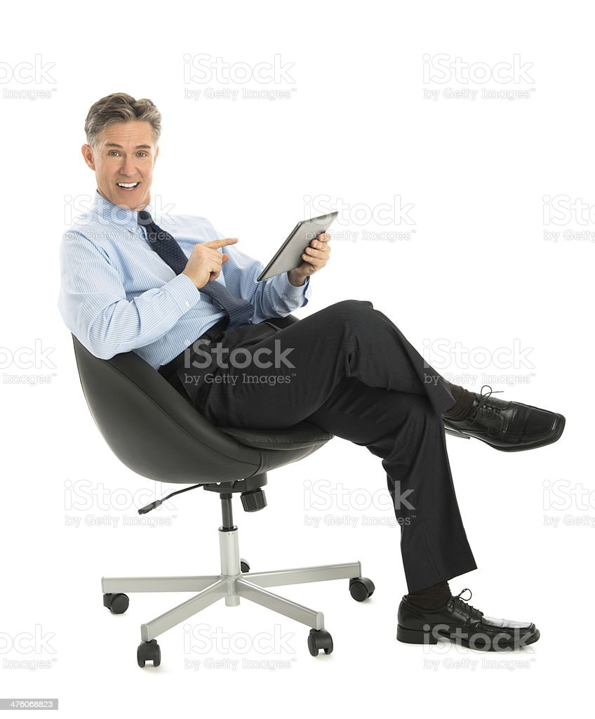 Businessman Pointing At Digital Tablet While Sitting On Office C stock photo