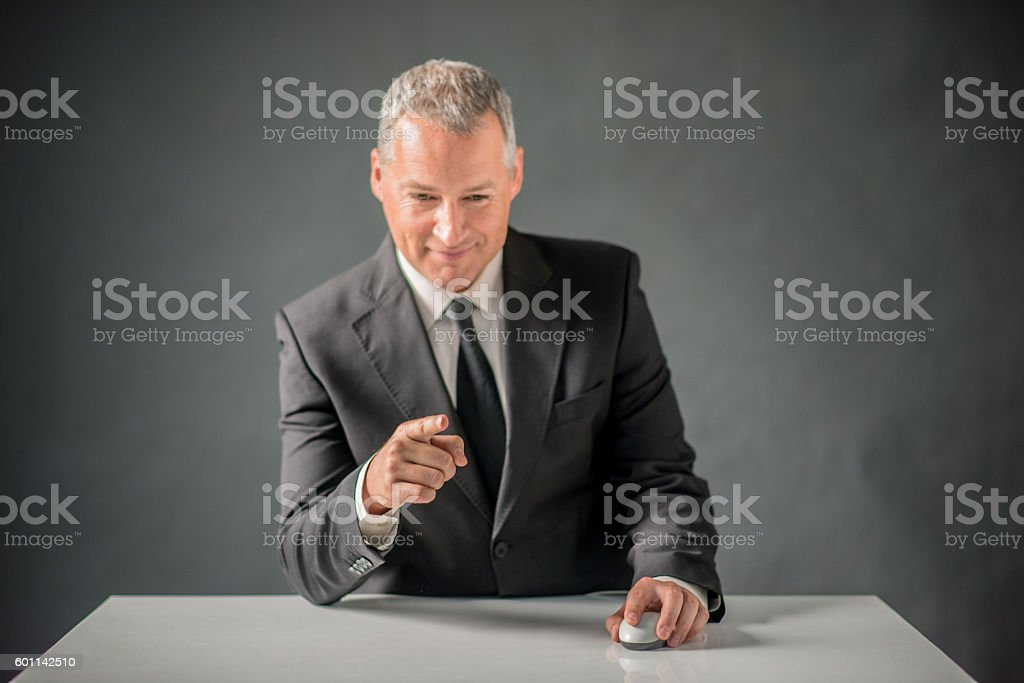 Businessman pointing at something and holding computer mouse ove stock photo