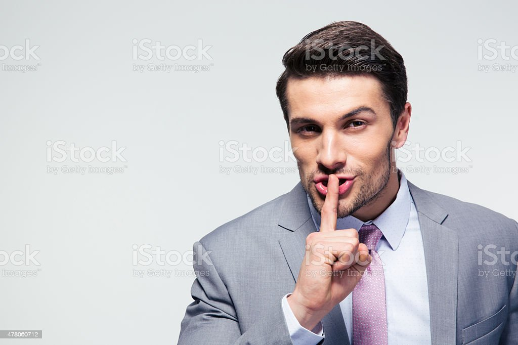 Businessman pointing finger over lips, asking for silence stock photo