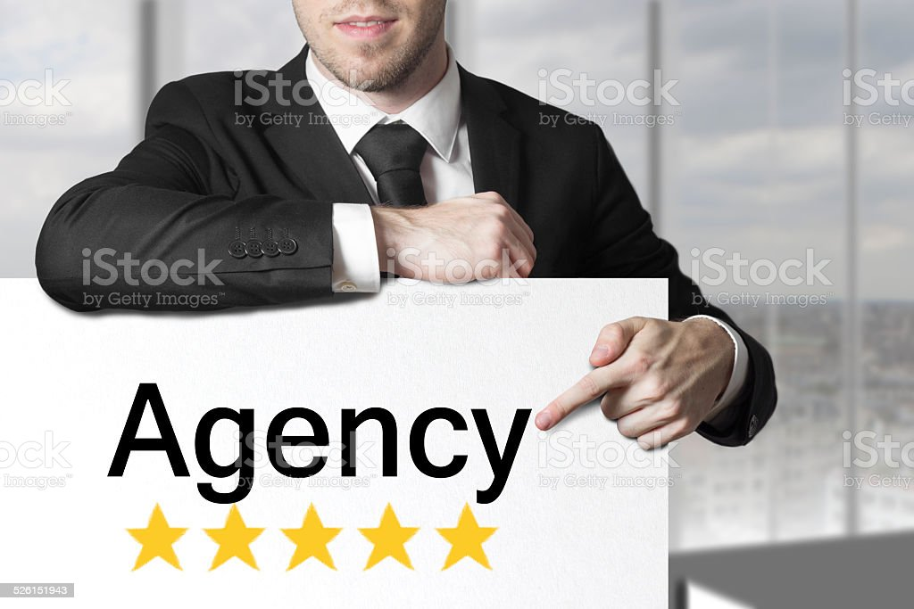 businessman pointing on sign agency stock photo