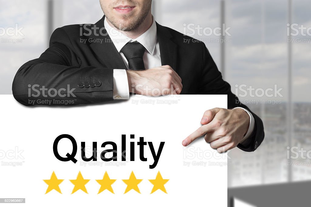 businessman pointing on sign quality stock photo