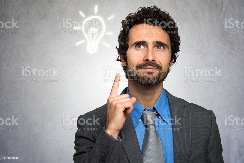 Businessman pointing to lightbulb above head in idea concept stock photo