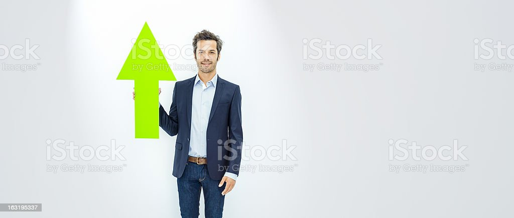 Businessman pointing up with green arrow stock photo