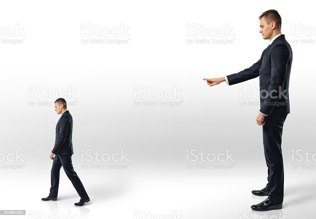 Businessman points at another man following in the direction indicated. stock photo