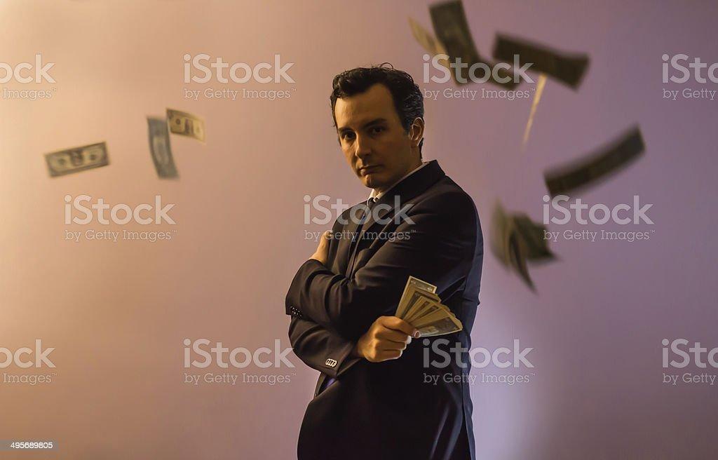Businessman Posing Among Dollars stock photo