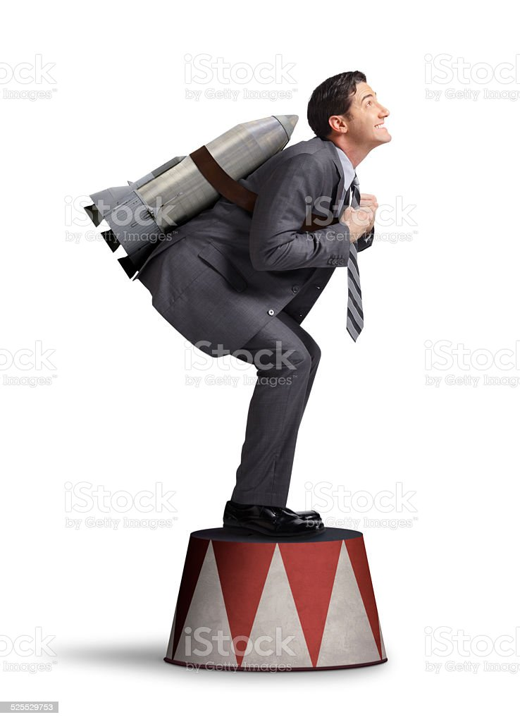 Businessman Preparing For Take Off On Circus Pedestal stock photo