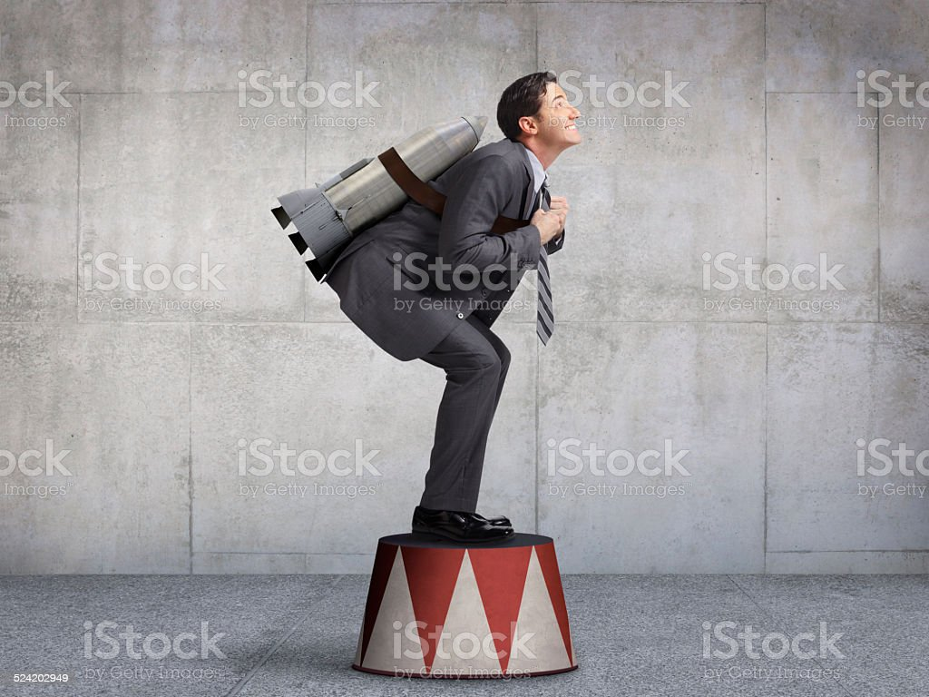 Businessman Preparing For Takeoff On Circus Pedestal stock photo