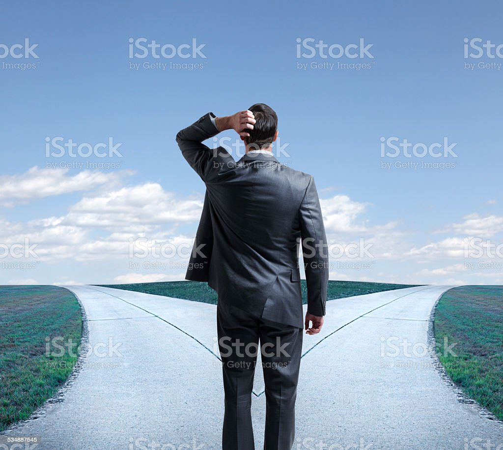 Businessman presented with the proverbial fork in the road stock photo