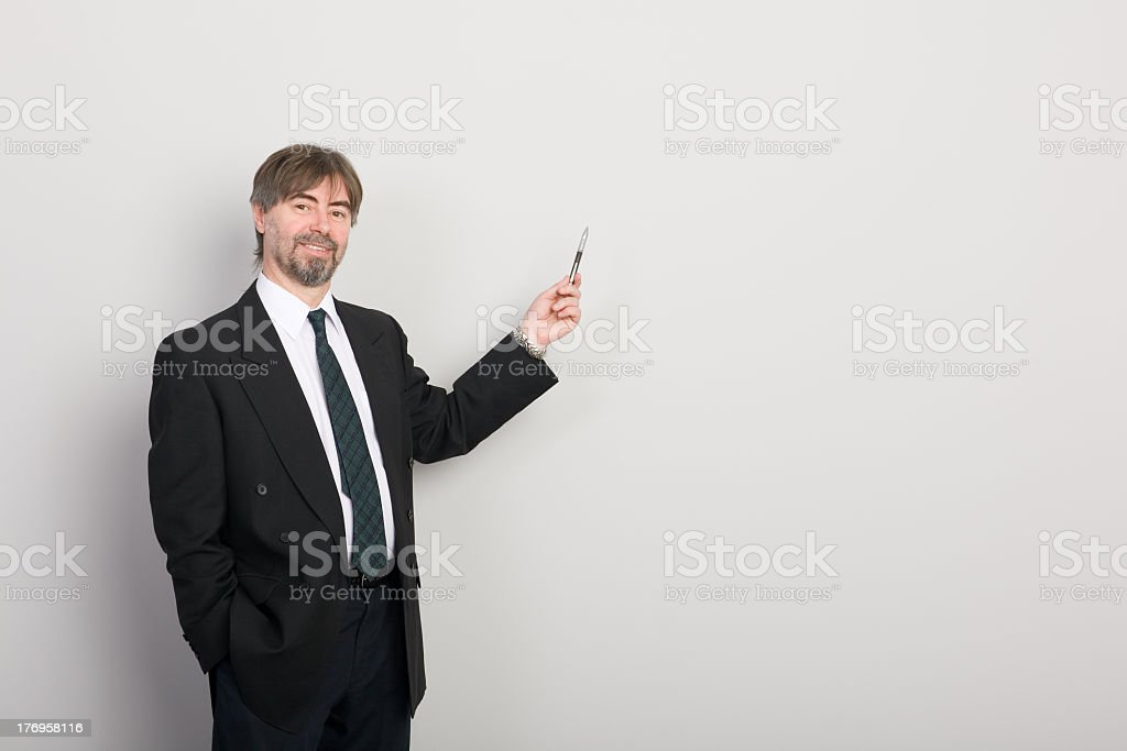 Businessman presenting an idea on a white wall stock photo