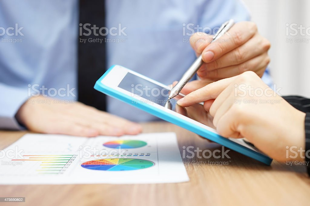 Businessman presenting document to client on tablet computer stock photo