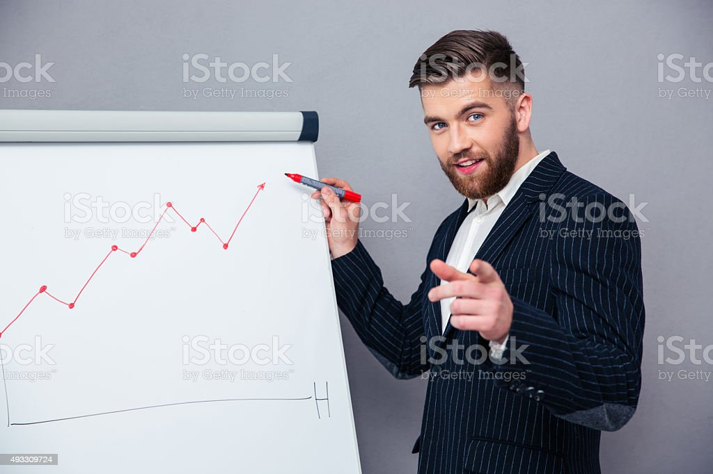 Businessman presenting something on board stock photo