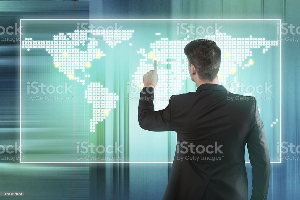 Businessman pressing location on a world map screen royalty-free stock photo
