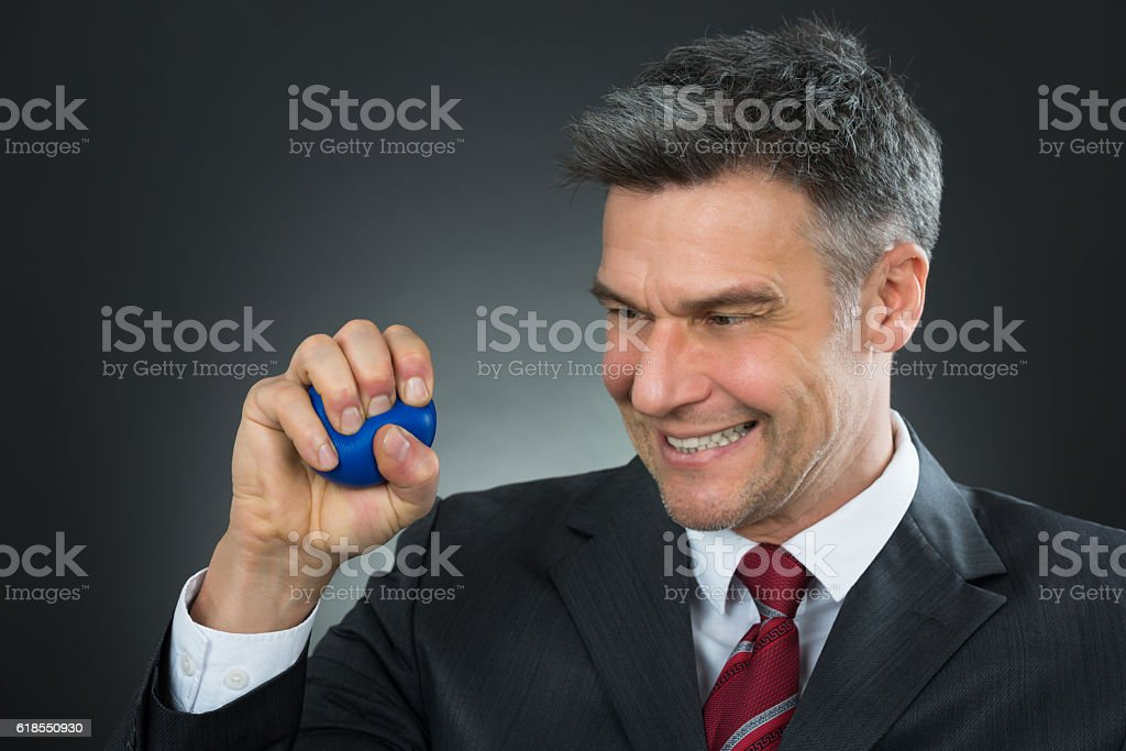 Businessman Pressing Stressball In Hand stock photo