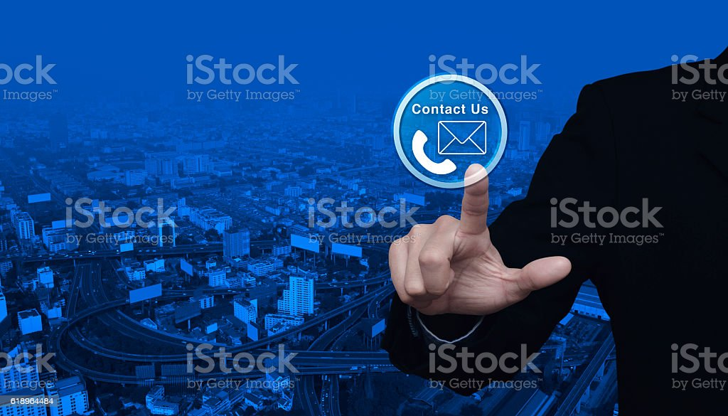 Businessman pressing telephone and mail icon button over city street stock photo
