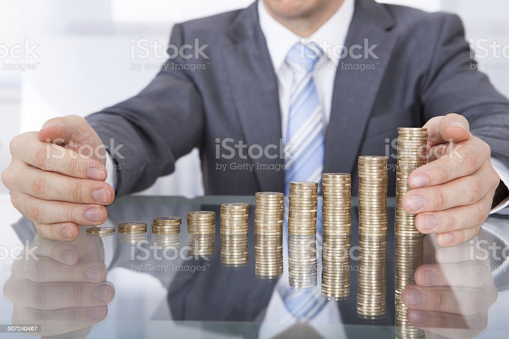 Businessman Protect Stack Of Coins stock photo