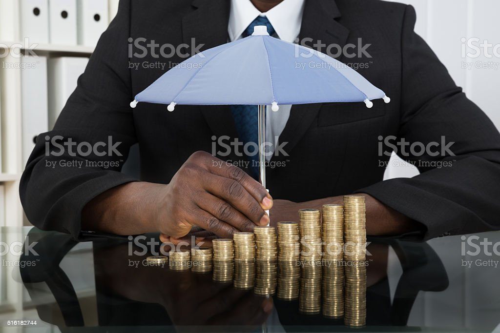 Businessman Protecting Coins With Umbrella stock photo