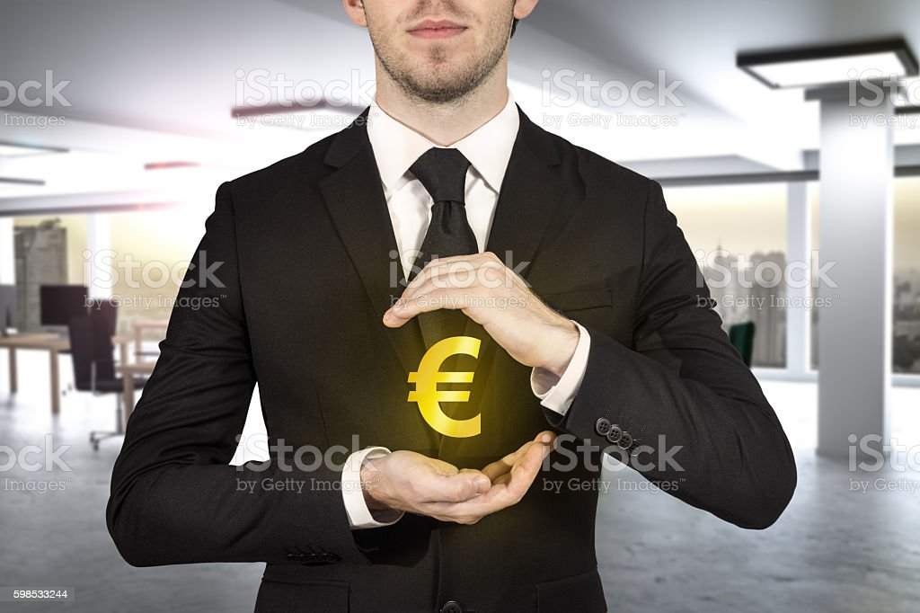 businessman protecting golden eurosymbol stock photo