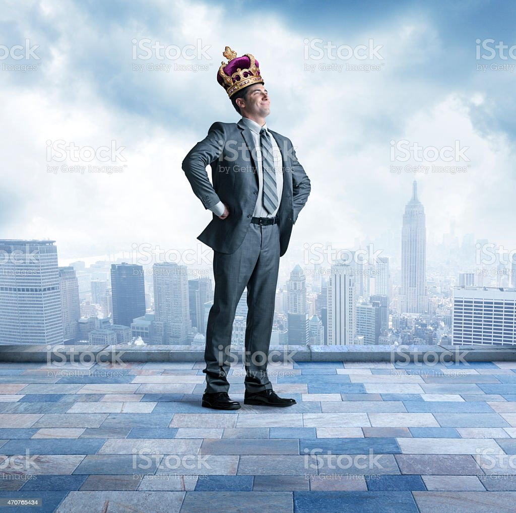Businessman proudly wearing a crown above big city skyline stock photo