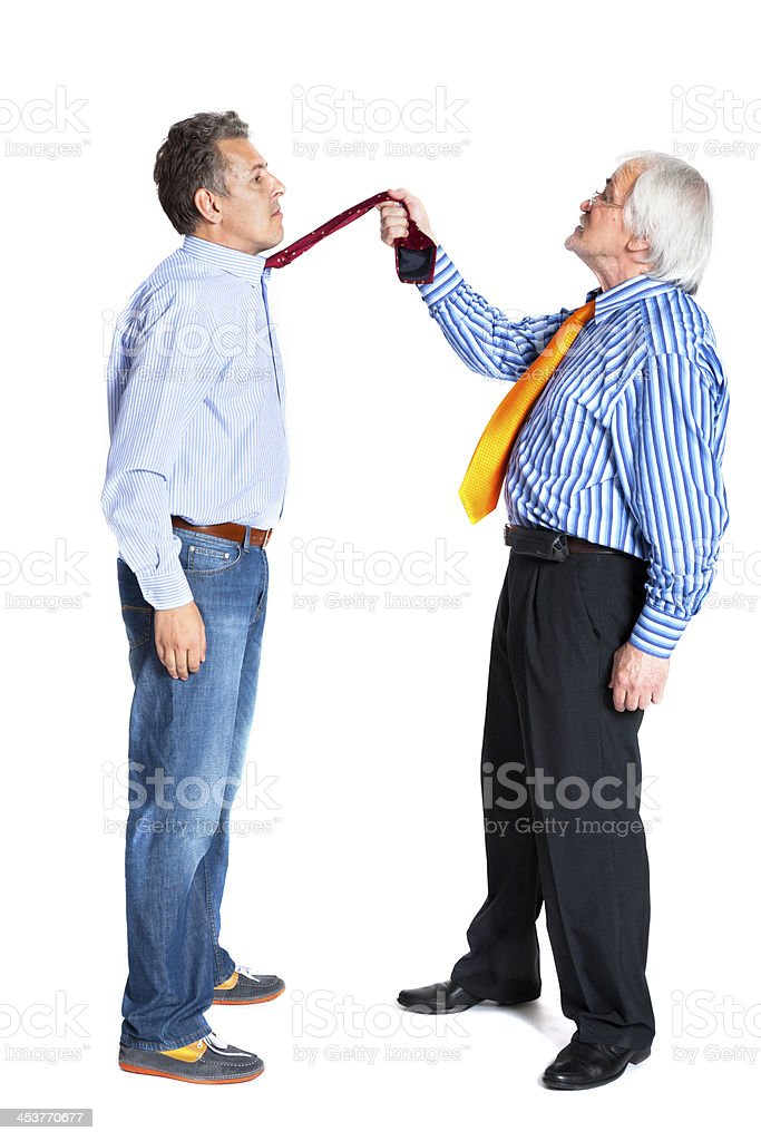 businessman pulling a tie to younger man royalty-free stock photo
