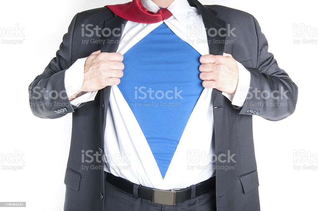 Businessman pulling apart shirt to reveal he is a superhero stock photo