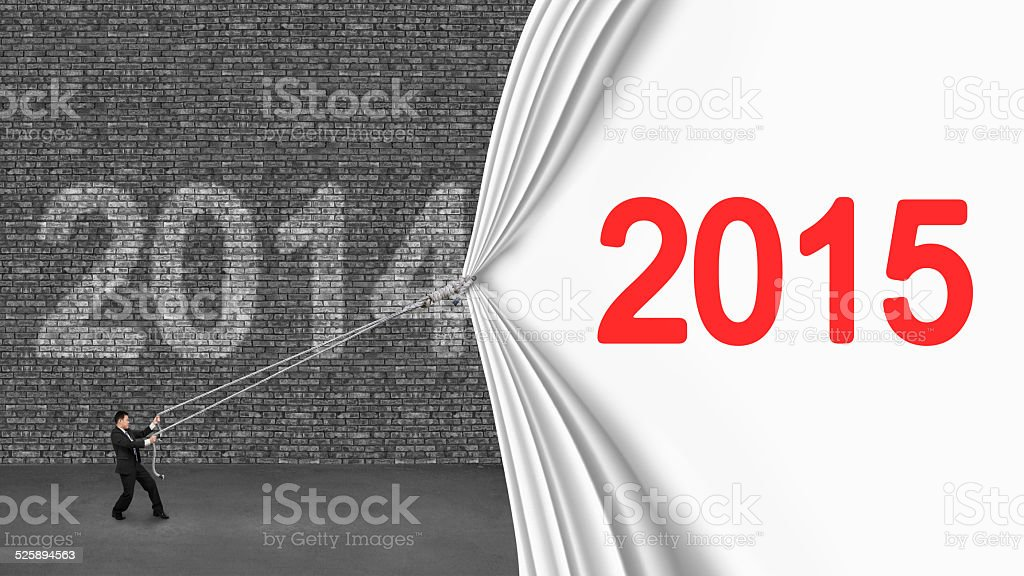 businessman pulling down 2015 curtain covering old 2014 brick wa stock photo