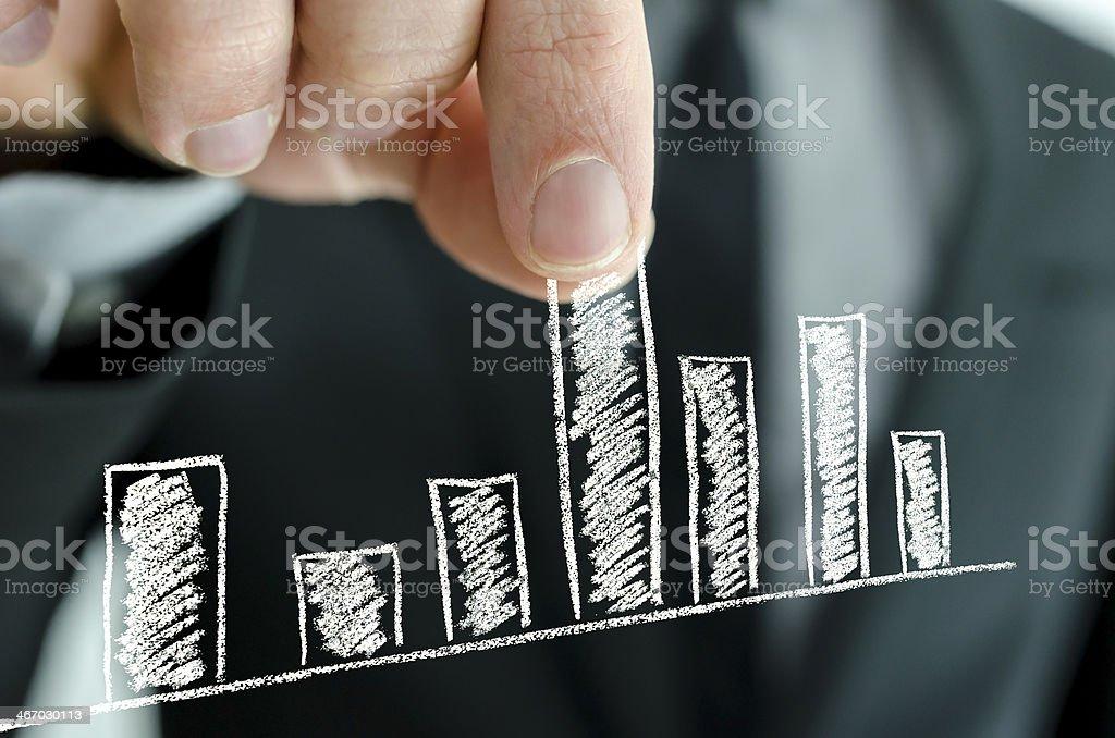 Businessman pulling graph column upwards stock photo