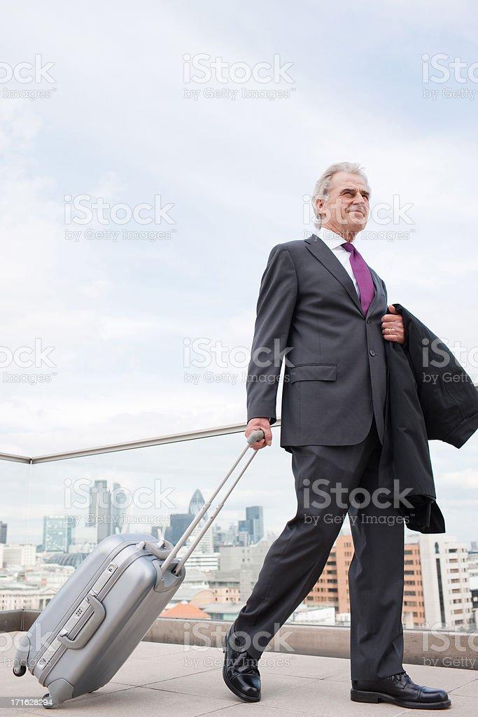 Businessman pulling luggage across urban balcony royalty-free stock photo