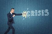 Businessman punching hard the word 'crisis' written on dark blue