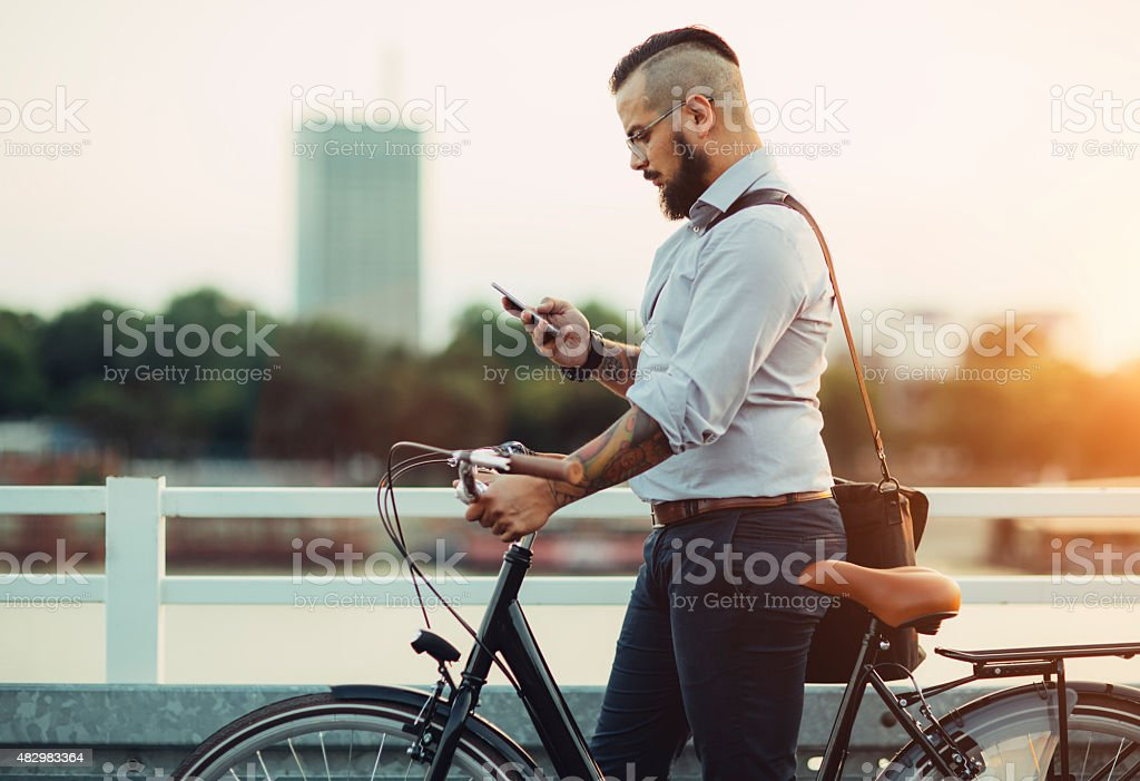 Businessman Push Bicycle and Using Smartphone Outdoors. stock photo