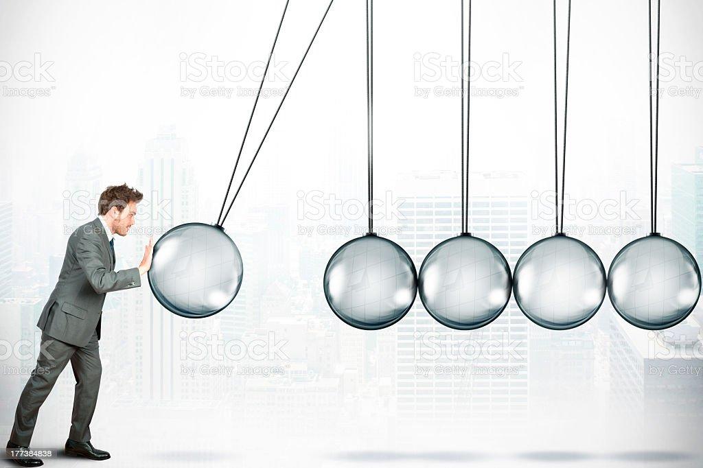 A businessman pushing a giant Newton ball stock photo