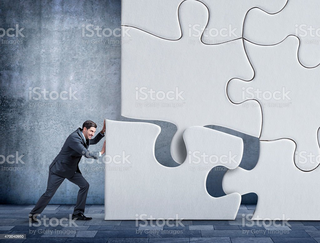 Businessman pushing a puzzle piece into place stock photo