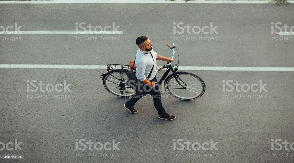 Businessman Pushing Bicycle and going home late. stock photo