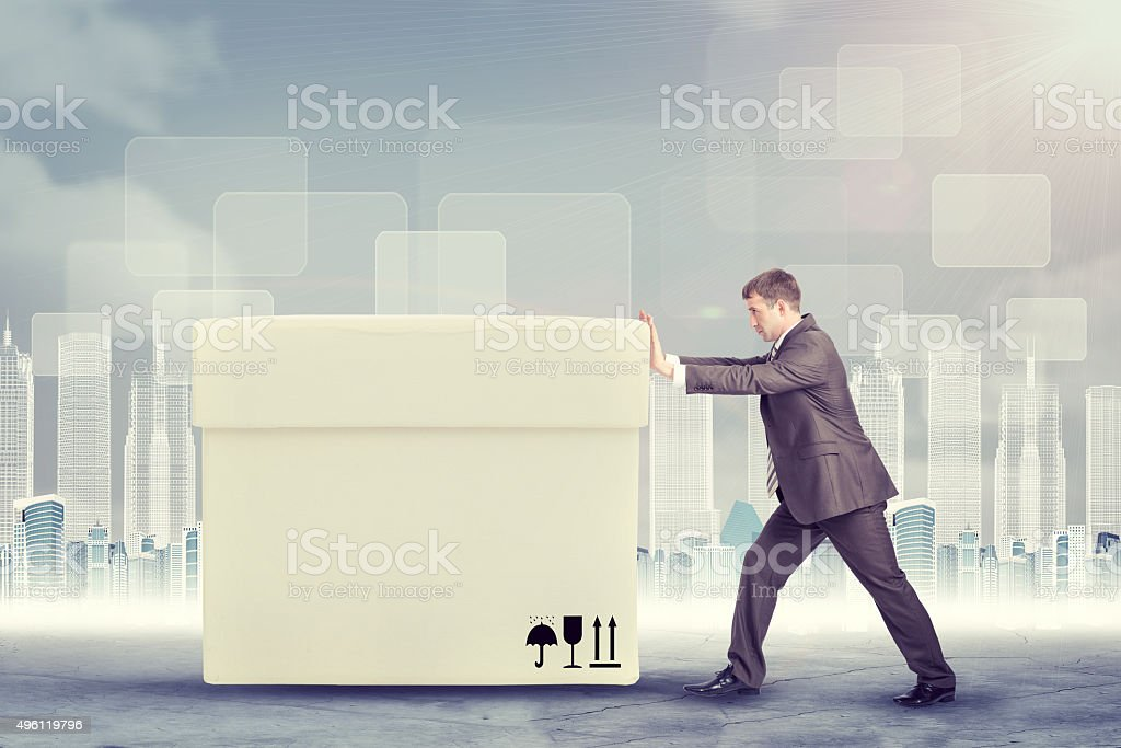 Businessman pushing big white box stock photo