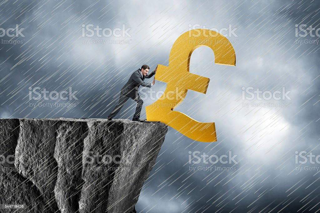 Businessman Pushing British Pound Symbol Over A Cliff stock photo