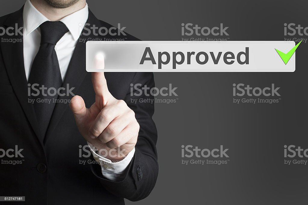 businessman pushing button approved green authorized stock photo