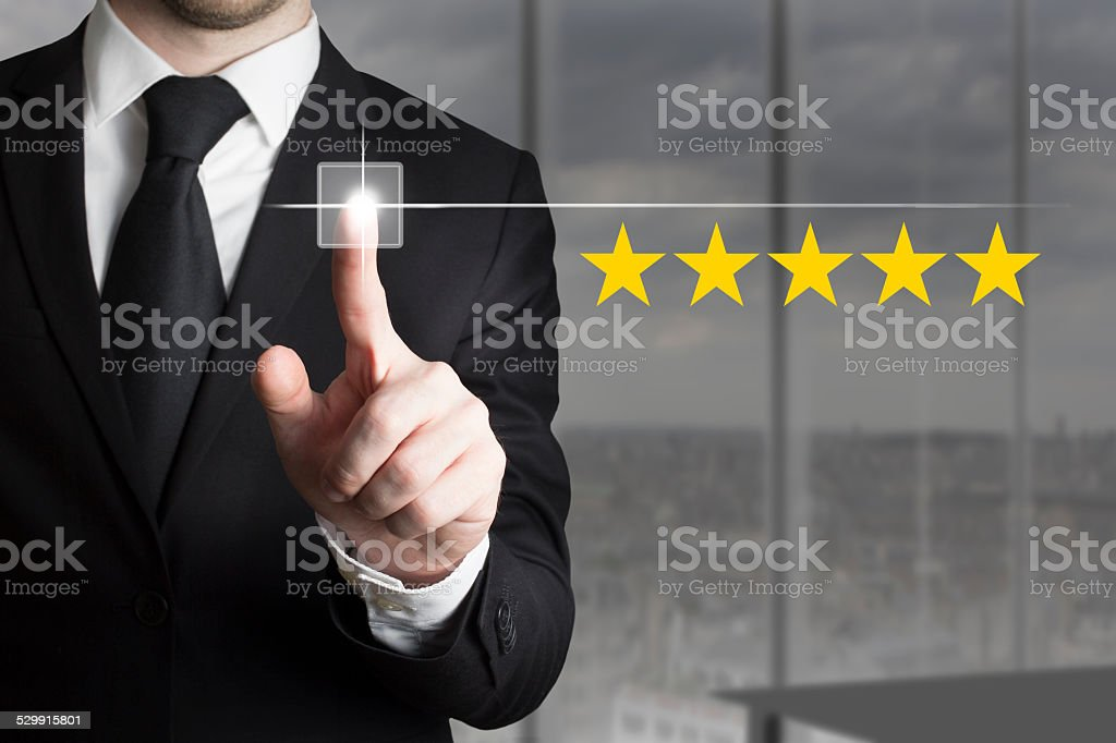 businessman pushing button five star rating stock photo