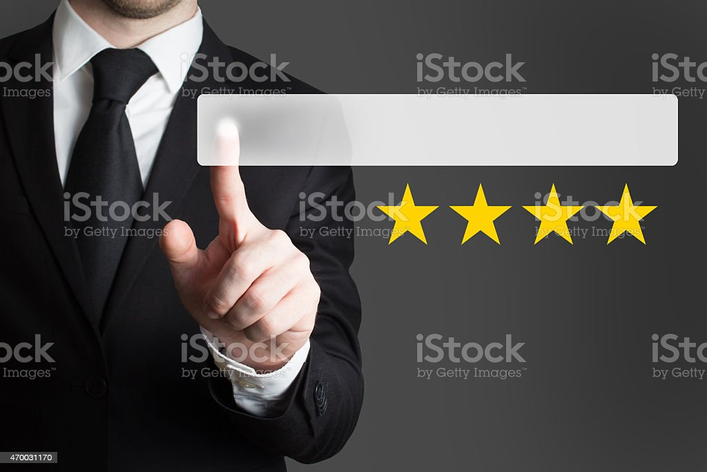 businessman pushing button four golden stars stock photo