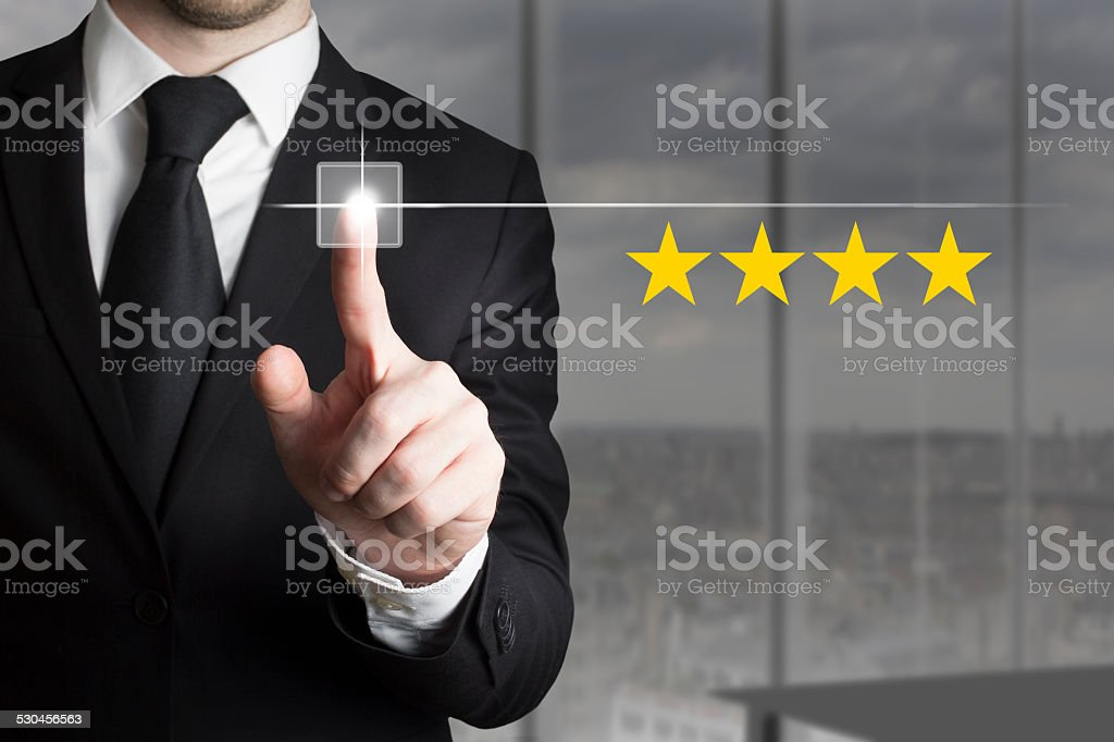 businessman pushing button four stars stock photo