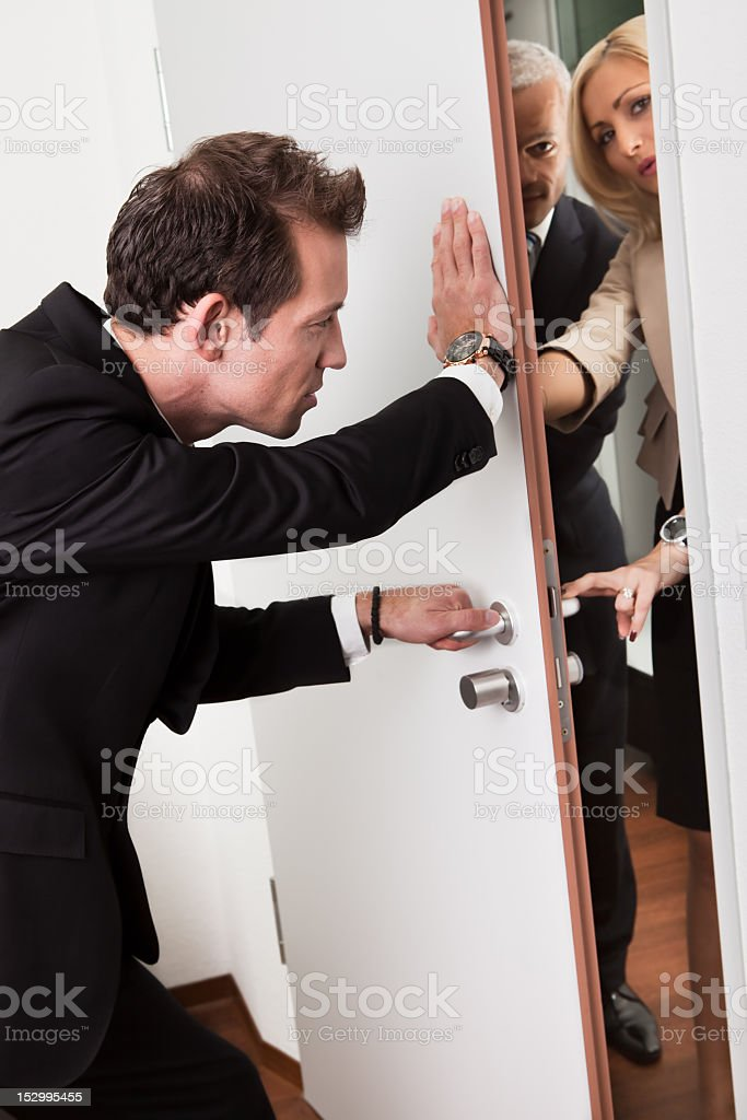 Businessman pushing door shut against demanding people stock photo