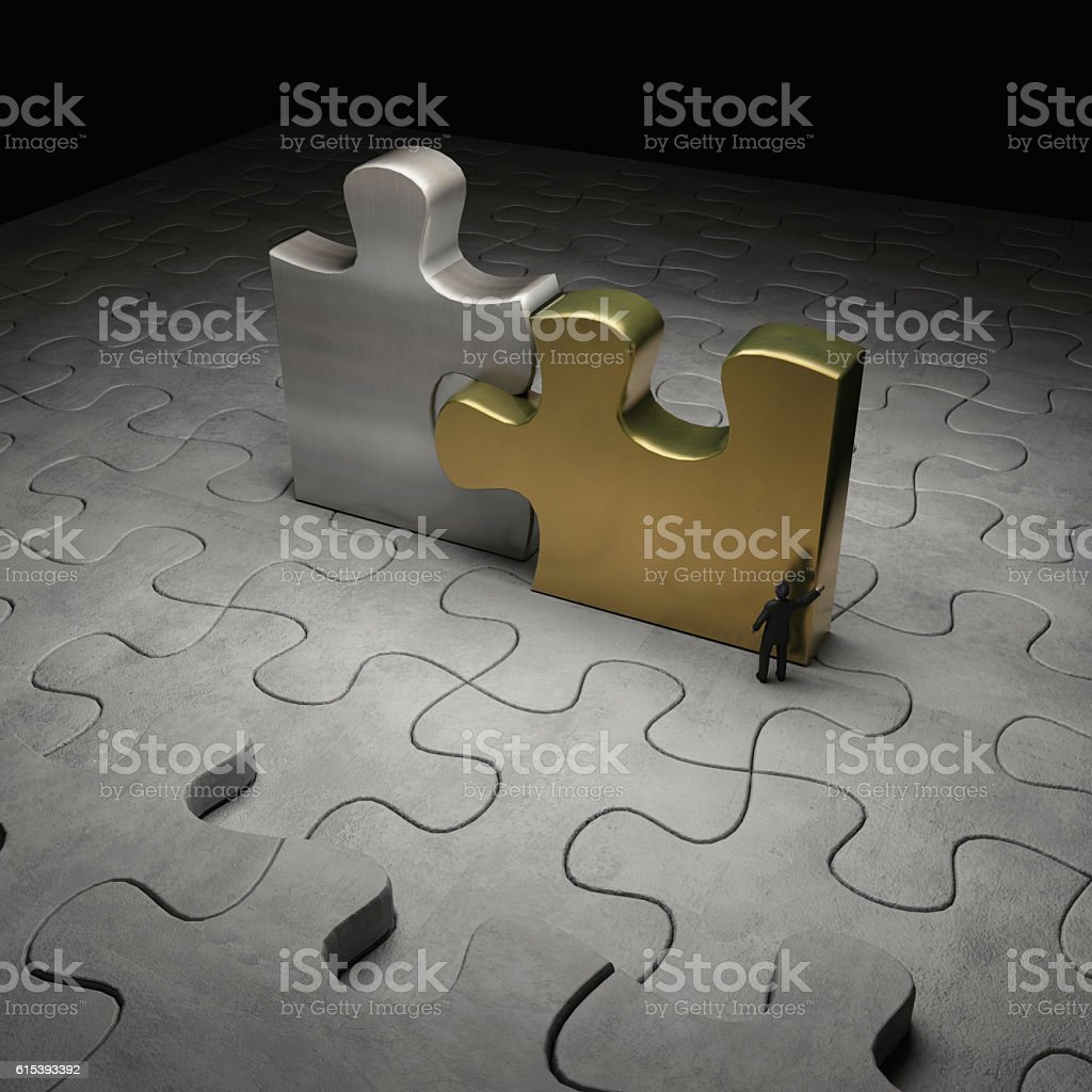 businessman pushing gold and silver big puzzle pieces stock photo